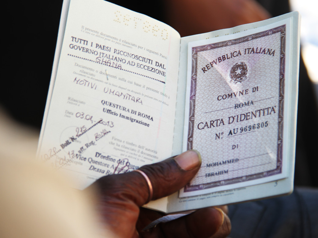 A migrant from Ghana holds up his documents